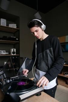 음악 가게. 비닐 레코드 구매. 헤드폰, 현대 턴테이블에서 오디오를 듣고 젊은 남성