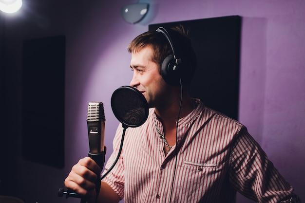 Концепция музыки, шоу-бизнеса, людей и голоса - мужская певица с наушниками и песней петь микрофона на студии звукозаписи.