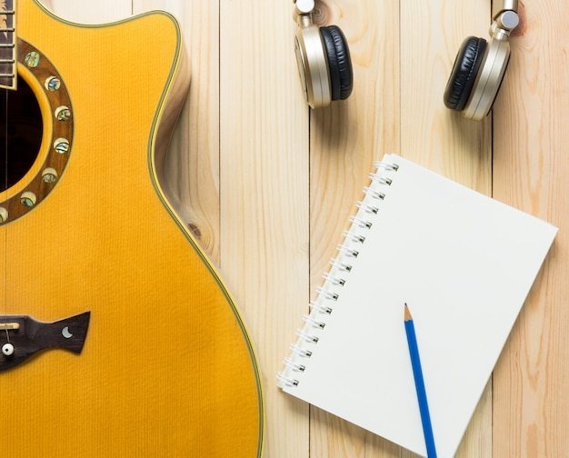 Music song writing equipment, blank book, guitar, headphone for song writing.