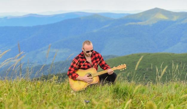 Музыка говорит. сексуальный мужчина с гитарой в клетчатой рубашке. хипстерская мода. западный кемпинг и походы. счастливы и свободны. ковбой человек с акустическим гитаристом. песня в стиле кантри.