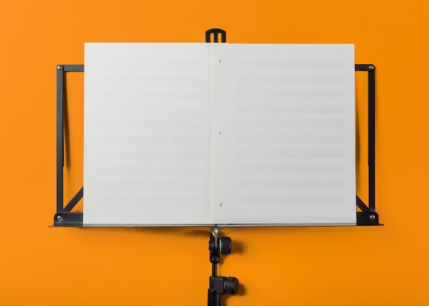 Music stand with blank white musical page on orange backdrop