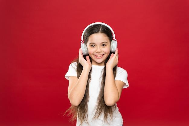 Музыкальный вкус. музыка играет важную роль в жизни подростков. мощно воздействует музыка на подростков на их эмоции, восприятие мира. девушка слушать музыку в наушниках на красном фоне. концепция списка воспроизведения.