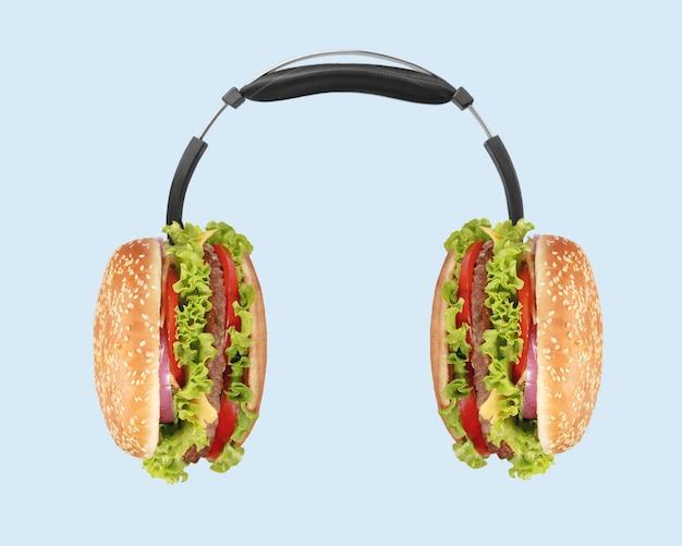 Музыка такая восхитительная на вкус. розовые наушники с гамбургерами как динамика на голубом фоне.