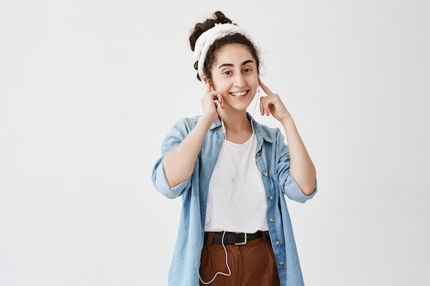 Music and technology concept. dark-haired girl listening to audiobook or radio on cell phone with earphones, looking and smiling  against white copy space wall for advertising content