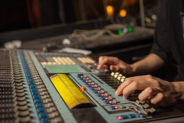 음악, 기술, 사람 및 장비 개념 - 조명 위에 사운드 녹음 스튜디오에서 믹싱 콘솔에 있는 남자.