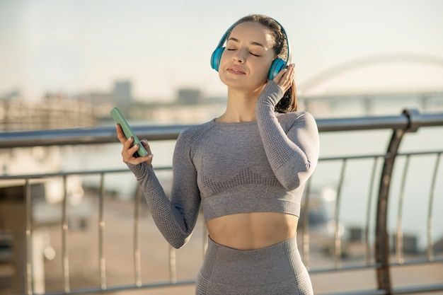 Время музыки. подходящая девушка в серой спортивной одежде слушает музыку и выглядит задумчивой