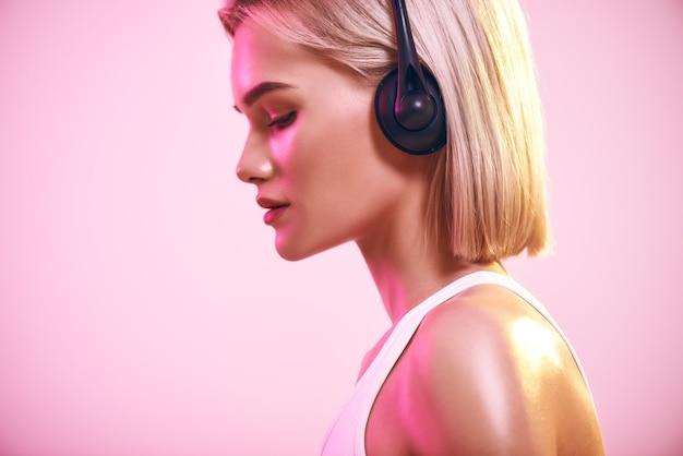 Музыкальные волны вид сбоку красивой блондинки в наушниках, слушающей музыку, стоя против