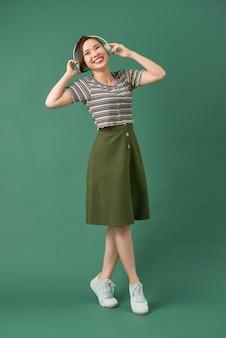 孤立した緑に対して踊る音楽の若い女の子