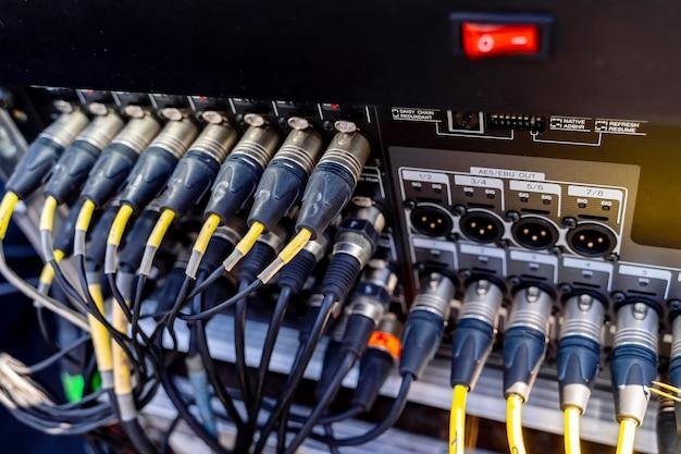 コンサートの音楽機器。コネクターはオーディオミキサーに接続されています。閉じる。