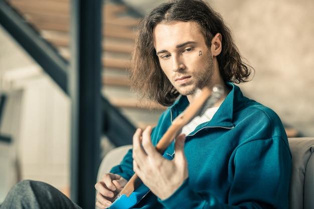 楽器。感情のない長髪の変わった男が、居間のソファに座りながら音楽の繰り返しを始める