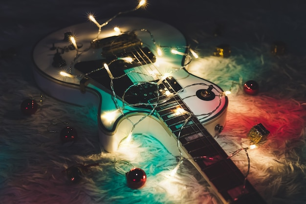 어두운 배경에 악기입니다. 어두운 배경에 불이 켜진 화환이 있는 일렉트릭 기타입니다. 크리스마스 또는 새해를 위한 선물 기타 클래식 모양.