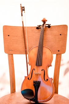 Musical instrument small children violin with bow stands on old wooden chair. concept musical