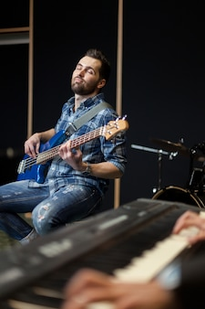 Musical keyboard and guitarist on chair
