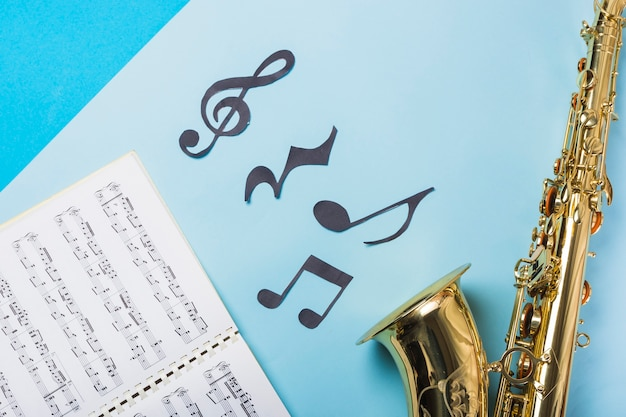 Musical notebook and golden saxophones on blue backdrop