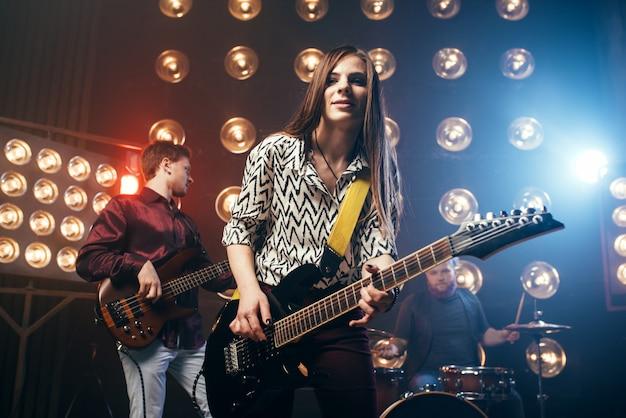 Музыкальные исполнители на сцене в ночном клубе, винтажном стиле. гитаристы и барабанщик, концерт рок-группы, музыкальное шоу