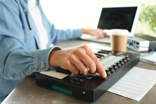 Музыкальный продюсер работает на своем рабочем месте на сером текстурированном столе