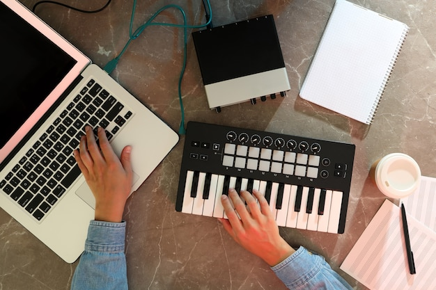 Музыкальный продюсер, работающий на своем рабочем месте, вид сверху