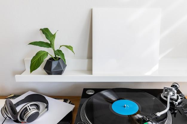 Lpカバーのビニールレコードターンテーブルプレーヤー空白の正方形の紙のカードボックスと音楽のテーマのモックアップと