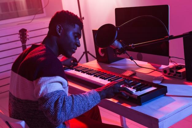 ミュージシャンと音楽コンセプトの作成-レコーディングスタジオで働くアフリカ系アメリカ人の男性サウンドプロデューサー