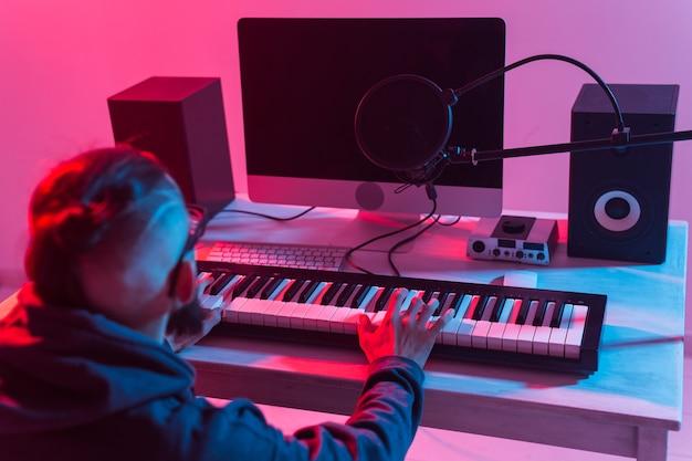 ミュージシャンと音楽のコンセプトを作る。レコーディングスタジオで働く男性のサウンドプロデューサー。