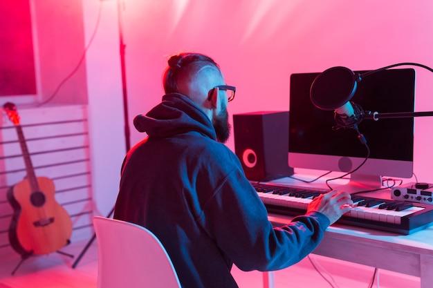 ミュージシャンと音楽コンセプトの作成-レコーディングスタジオで働く男性のサウンドプロデューサー。