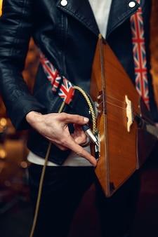 ミュージシャンがバラライカをつなぎ、ステージで演奏する音楽