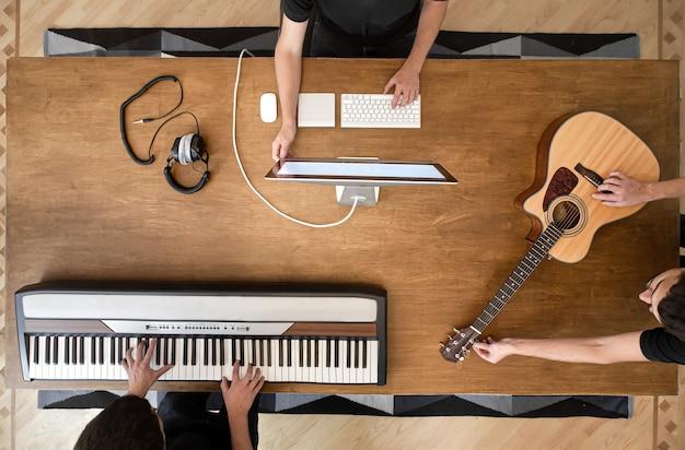 Музыкант создает музыку в своей студии, играя на клавишных и акустической гитаре. процесс работы над звуком на деревянном столе.