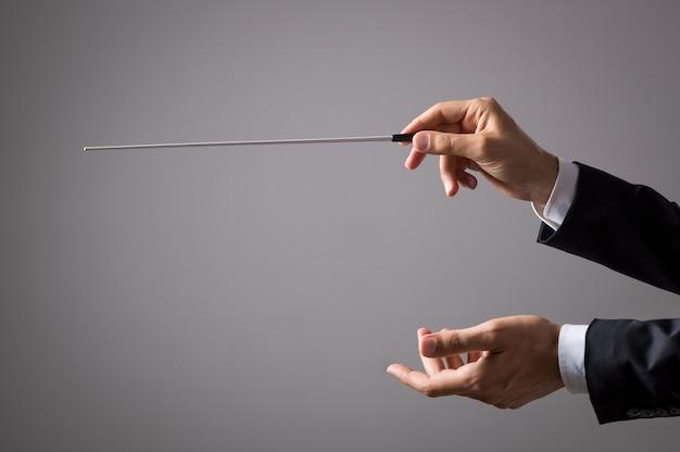 Музыкант-режиссер держит палку, изолированную на сером