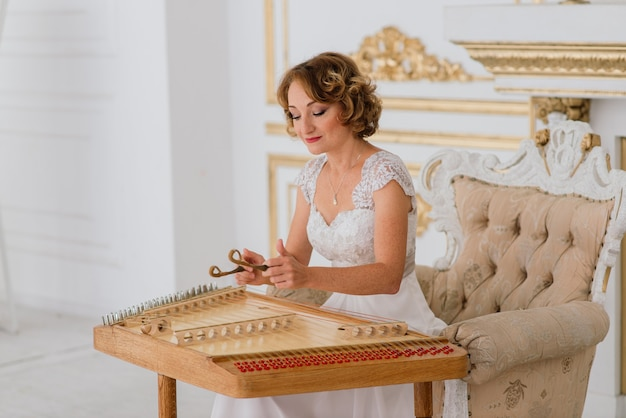 Musician female play dulcimer traditional instrument in interior