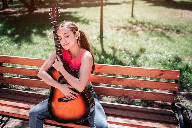 Musician girl is sitting on bench and holding guitar. she is leaning to it. girl has closed her eyes and enjoying the moment.