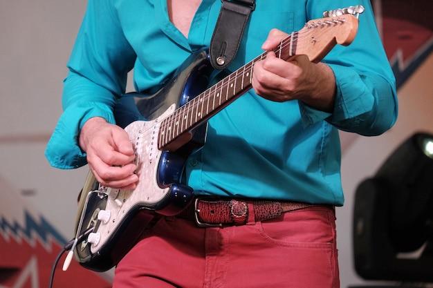 青いシャツと赤いジーンズを着たミュージシャンのギタープレーヤーがエレキギターでステージで演奏します