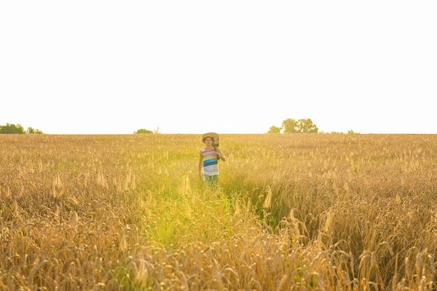 Музыкант держит акустическую гитару и гуляет по летним полям на закате