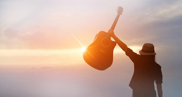 Musician holding acoustic guitar in hand on sunset