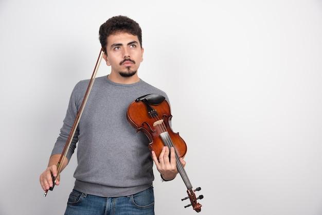 바이올린을 들고 연주 할 다음 곡에 대해 생각하는 음악가. 무료 사진