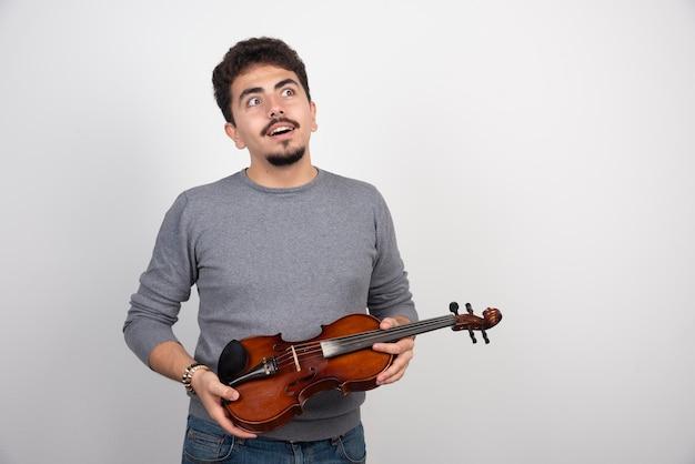 Musicista che tiene il violino e pensa al prossimo pezzo da suonare.