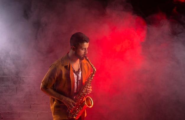 Музыкант в тумане играет на саксофоне