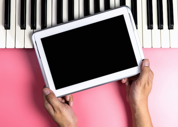 Musician is holding blank tablet screen for music application mock up