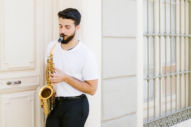 Музыкант, прислонившись к стене, играет на саксофоне