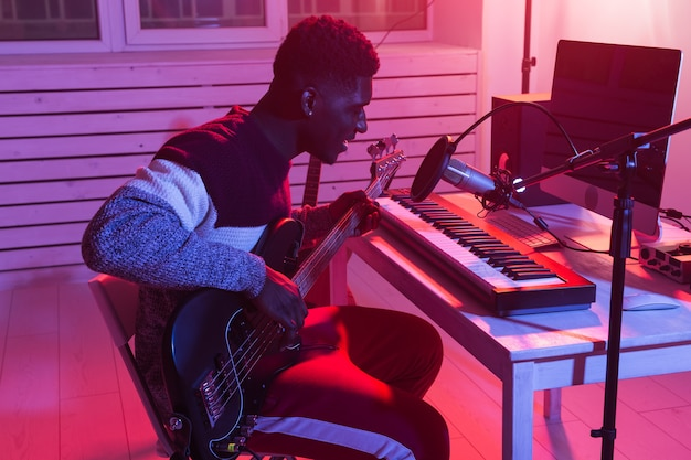 Musician and making music concept - african american male sound producer working in recording studio.