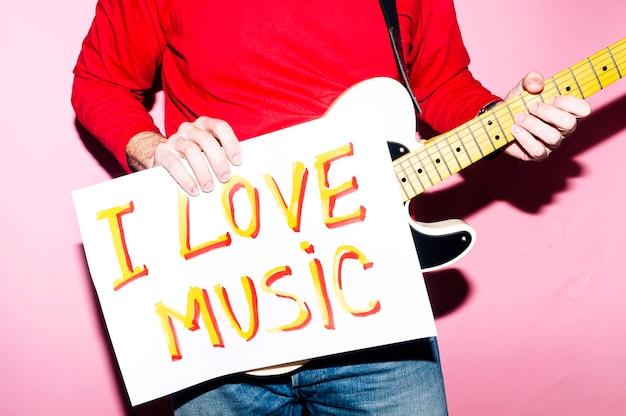 私は音楽が大好きだと言うギターとサインを持つミュージシャンの男