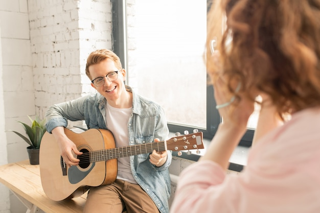 Musician man with guitar singing for her girlfriend