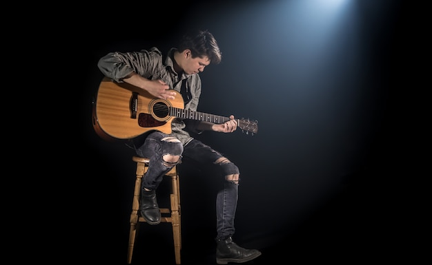 Музыкант играет на акустической гитаре, сидя на высоком стуле, черный фон с красивым мягким светом