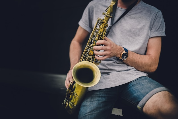 Музыкант играет альт-саксофон на концерте.