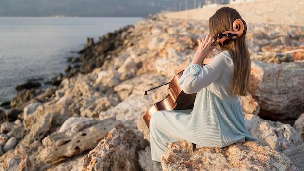 바위에 일몰에 첼로 연주 음악가
