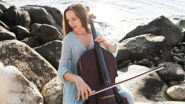 海でチェロを弾くミュージシャン