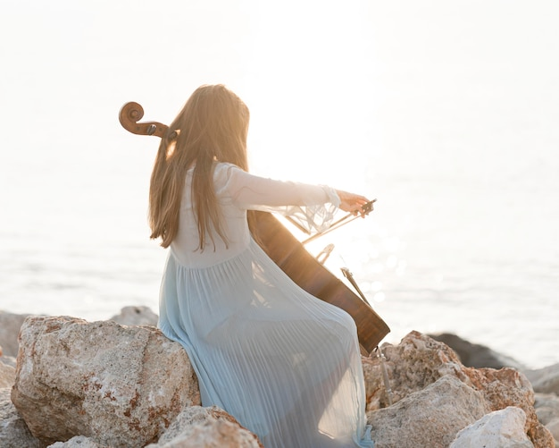 海沿いの岩の上でチェロを演奏するミュージシャン