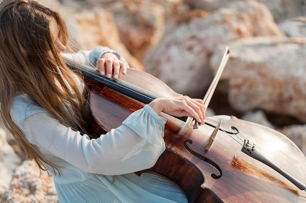 岩の上でチェロを弾くミュージシャン