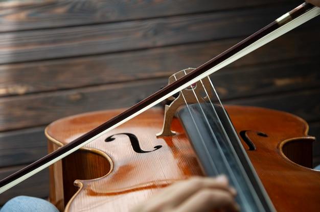 Музыкант играет на виолончели на деревянном полу