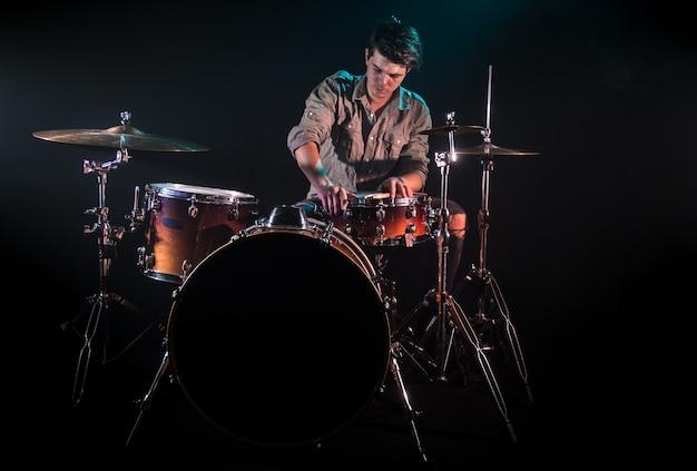 드럼, 검정색 배경 및 아름다운 부드러운 빛, 감정적 인 놀이, 음악 개념을 연주하는 음악가