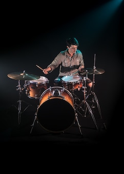 Музыкант играет на барабанах, черный фон и красивый мягкий свет, эмоциональная игра, музыкальная концепция
